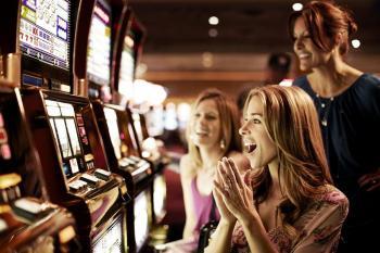 Naisia pelaamassa pelikoneita